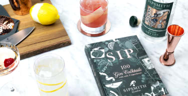 Cocktails, ingredients and cocktail-making tools scattered on a marble surface next to Sipsmith's SIP book
