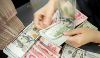 A Chinese bank employee counts 100-yuan notes and US dollar bills at a bank counter.