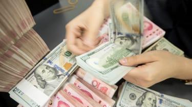 A Chinese bank employee counts 100-yuan notes and US dollar bills at a bank counter.