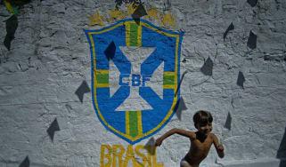 A boy runs past graffitti showing the Brazil logo