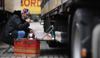A truck drinks tea next to his freight truck at the Motis freight clearance centre.