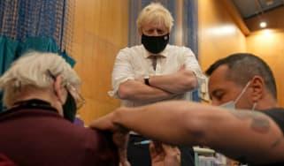 Boris Johnson watches a patient receive a booster jab