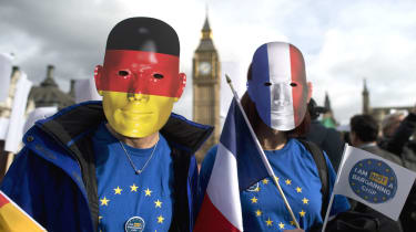 Pro-migrant protesters wearing German and French flag face masks outside Parliament in 2017