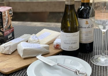A cheese spread and two bottles of wine