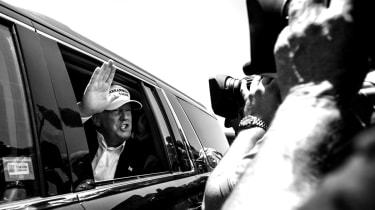 """LAREDO, TEXAS - JULY 23: Republican Presidential candidate and business mogul Donald Trump talks to media from his car wearing a, """"Make America Great Again,"""" hat during his trip to the border"""