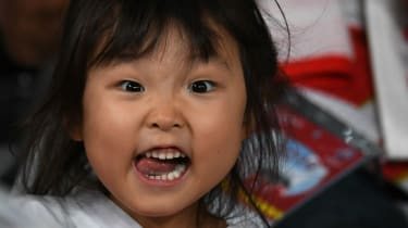 A young Japanese fan cheers during the opening ceremony at the Tokyo Stadium