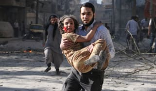 A man carries a wounded girl following a 'barrel bomb' attack in Aleppo