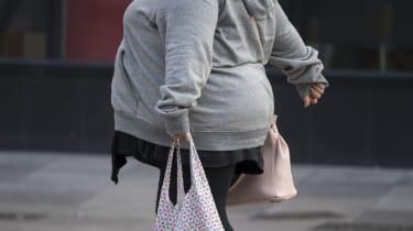 Obese woman walking on pavement