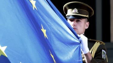 A Lithuanian soldier holds the flag of the European Union during a ceremony in front of the governmental palace in Vilnius on July 1, 2013. The small Baltic nation, the first to break free fr