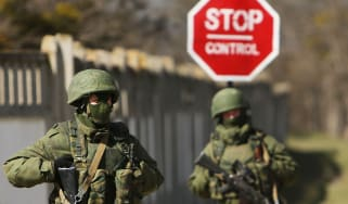 Armed soldiers without identifying insignia stand guard outside a Ukrainian military base in Crimea