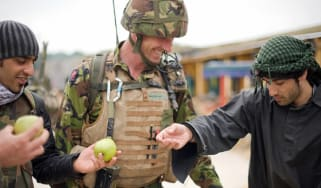 """A British soldier (C) and his interpreter (L) talk with an Afghan actor playing the part of a villager during a training exercise in a new """"Afghan village"""" at a military base in Norfolk, in e"""