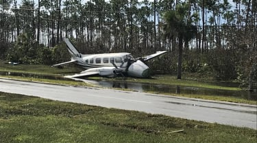 A damaged plane on the ground among trees