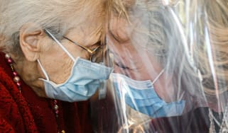 Two elderly people wearing face masks are reunited.