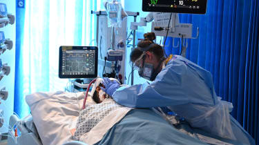A nurse wearing PPE cares for a patient in intensive care
