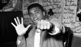 27th May 1963:Supremely confident American boxer Cassius Clay holds up five fingers in a prediction of how many rounds it will take him to knock out British boxer Henry Cooper.(Photo by Kent