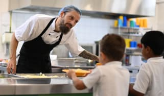 A school chef serves cooked hot dinner to students on their lunch break