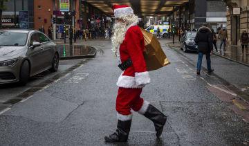 A man dressed as Santa Claus walks through Manchester city centre