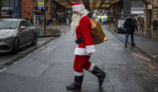 A man dressed as Santa Claus walks through Manchester city centre.