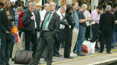 Passengers wait for trains to arrive, London