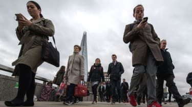 Commuters check their phone crossing London Bridge
