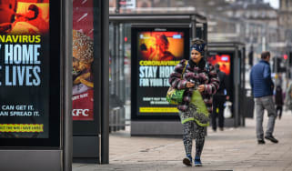 A member of the public walks in front of government lockdown advertisements in Edinburgh