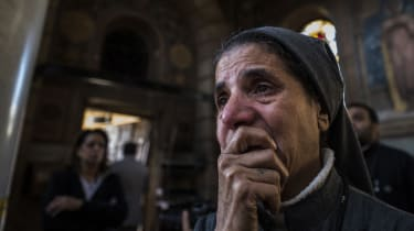 A nun reacts as Egyptian security forces (unseen) inspect the scene of a bomb explosion at the Saint Peter and Saint Paul Coptic Orthodox Church on December 11, 2016, in Cairo's Abbasiya neig