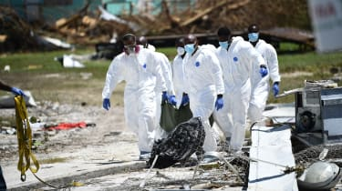 White-clad rescue workers carry a body in a black bag