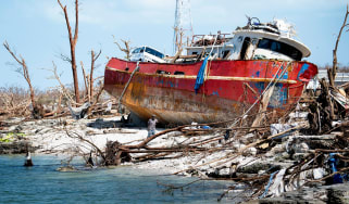 A damaged red boat sits on the shore among rubble