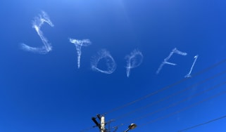 The words 'stop F1' are seen over the sky in Sydney, Australia on 11 March