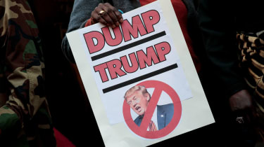 A woman holds an anti-Trump sign at a protest in 2016