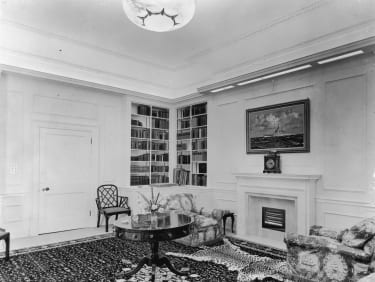 The library of Clarence House in London, 1949. The house was built in 1825-27 by John Nash for the Duke of Clarence, later King William IV. The painting above the fireplace is the HMS Vanguar