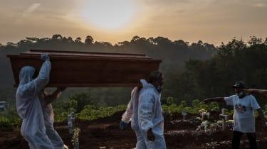 Grave diggers bury a coffin in Semarang, Java