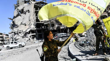 Syrian Democratic Forces fighter plants their flag at the centre of Raqqa