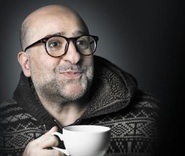 Omid Djalili holding a coffee cup