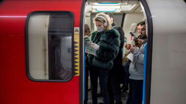 A commuter wears a mask while travelling on the London Underground