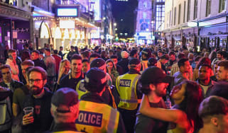 Police make their way through crowds of revellers during the pandemic in Soho, London