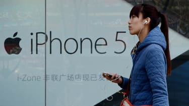 A Chinese woman listens to her iPhone outside an Apple reseller store in Beijing on April 2, 2013. Apple chief executive Tim Cook has apologised to Chinese consumers after the US technology g