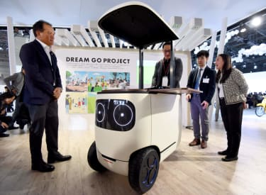 """Journalists try Honda's """"RoboCas Concept"""", electric mobility during the Tokyo Motor Show in Tokyo on October 25, 2017.RoboCas Concept is an electric cart with autonomous drive function./ AFP"""