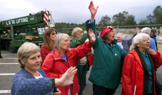 Peace campaigners wave as their caravan is taken away from outside the gates of Greenham Common on 5 September 2000