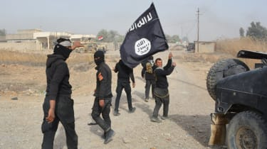 Iraqi government forces hold an Islamic State flag after they claimed they controlled an Islamic State town