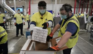 Boxes containing the Pfizer vaccine are prepared for shipping