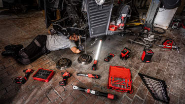 A man lying on the floor of a garage working on an engine and surrounded by Milwaukee tools