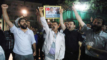 Supporters of Egyptian President Morsi shout slogans during a support rally in Ankara ON July 3, 2013. In Cairo, tens of thousands cheered, ignited firecrackers and honked horns as soon as th