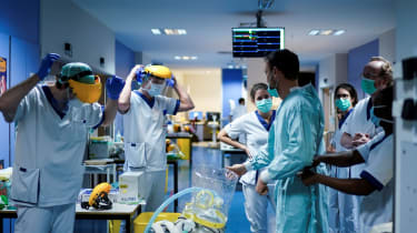 Medical workers put on their protective gears before working at the Erasme Hospital in Brussels.