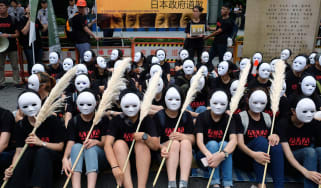 "Taiwanese NGO group members wear masks during a rally to demand that the Japanese government apologise to Taiwanese ""comfort women"" in Taipei on August 14, 2018. - Mainstream historians agree"