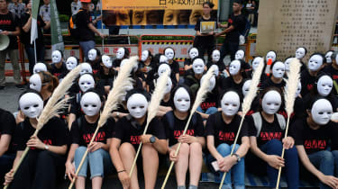 """Taiwanese NGO group members wear masks during a rally to demand that the Japanese government apologise to Taiwanese """"comfort women"""" in Taipei on August 14, 2018. - Mainstream historians agree"""