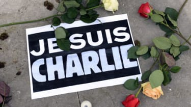 """A sign reading """"I am Charlie"""" lies on the ground with roses as people observe a minute of silence in Bordeaux, on January 8, 2015, as they remember the for the victims of an attack by armed g"""