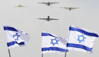 Israeli military planes fly over flags