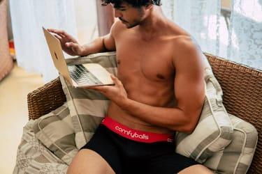Man wearing ComfyBalls underwear sat on sofa looking at laptop