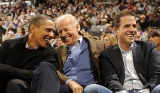 Barack Obama, Joe Biden and Hunter Biden talk during a college basketball game in 2010.